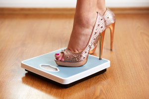 Female feet in golden stilettos with weight scale on wooden floor