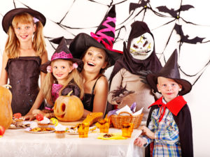 Halloween party with children holding carving pumkin.